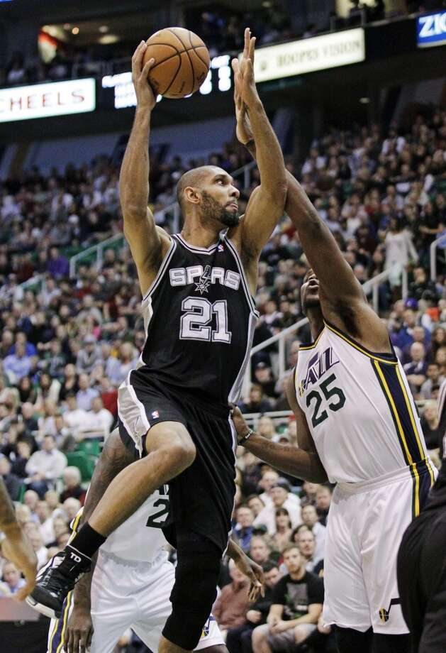 San Antonio Spurs forward Tim Duncan (21) shoots as Utah Jazz center Al Jefferson (25) defends in the first quarter during an NBA basketball game, Wednesday, Dec. 12, 2012, in Salt Lake City. (Rick Bowmer / Associated Press)