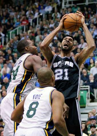 San Antonio Spurs forward Tim Duncan (21) goes to the basket as Utah Jazz forward Paul Millsap (24) and teammate guard Randy Foye (8) watch in the second quarter during an NBA basketball game Wednesday, Dec. 12, 2012, in Salt Lake City. (Rick Bowmer / Associated Press)