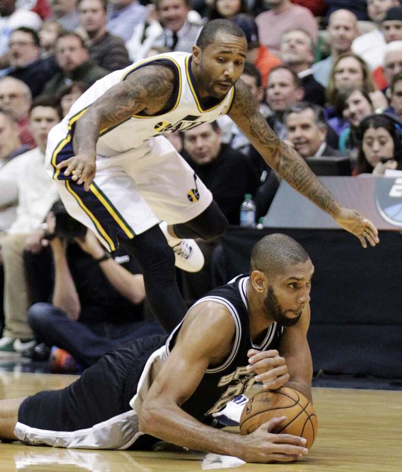 San Antonio Spurs forward Tim Duncan dives on a loose ball ahead of Utah Jazz guard Mo Williams in the first quarter during an NBA basketball game, Wednesday, Dec. 12, 2012, in Salt Lake City. (Rick Bowmer / Associated Press)