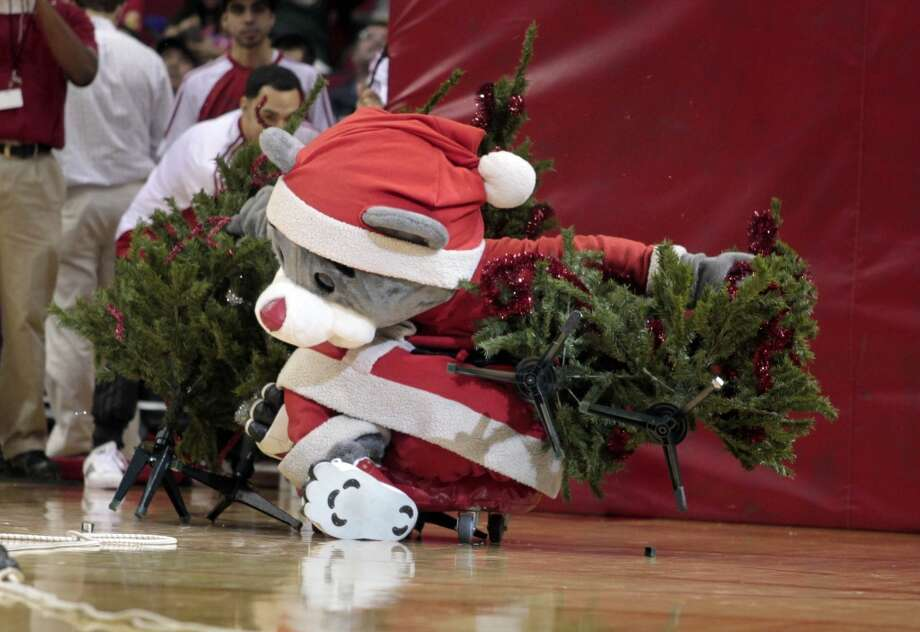 Rockets mascot Clutch knocks over Christmas trees in a game of Christmas tree bowling.