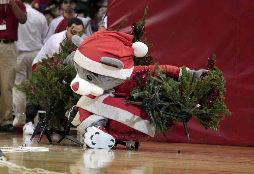 Rockets mascot Clutch knocks over Christmas trees in a game of Christmas tree bowling. (Billy Smith