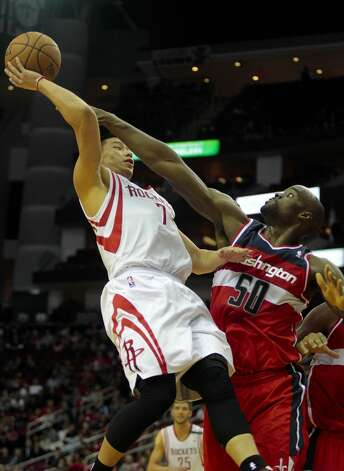 Rockets guard Jeremy Lin puts up a shot as Wizards center Emeka Okafor fouls him.   (Billy Smith II / Houston Chronicle)