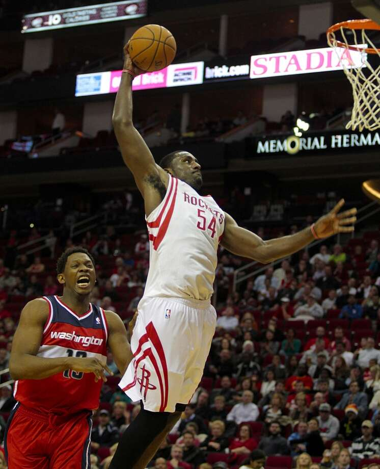 Rockets forward Patrick Patterson  dunks as Wizards center Kevin Seraphin trails on defense. (Billy Smith II / Houston Chronicle)