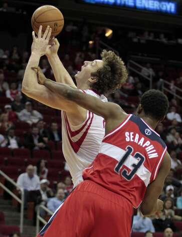 Rockets center Omer Asik shoots as Wizards center Kevin Seraphin defends.   (Billy Smith II / Houston Chronicle)