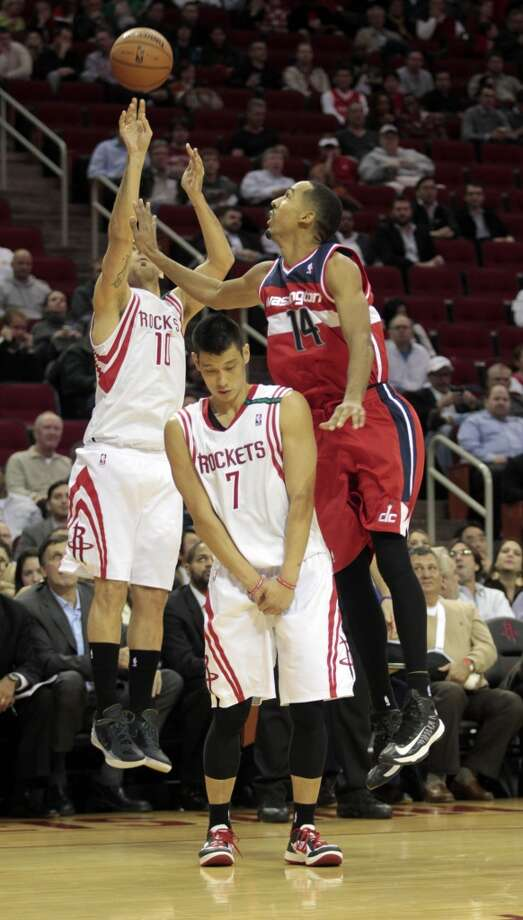 Rockets forward Carlos Delfino shoots a 3-pointer as Jeremy Lin screens Wizards guard Shaun Livingston. (Billy Smith II / Houston Chronicle)