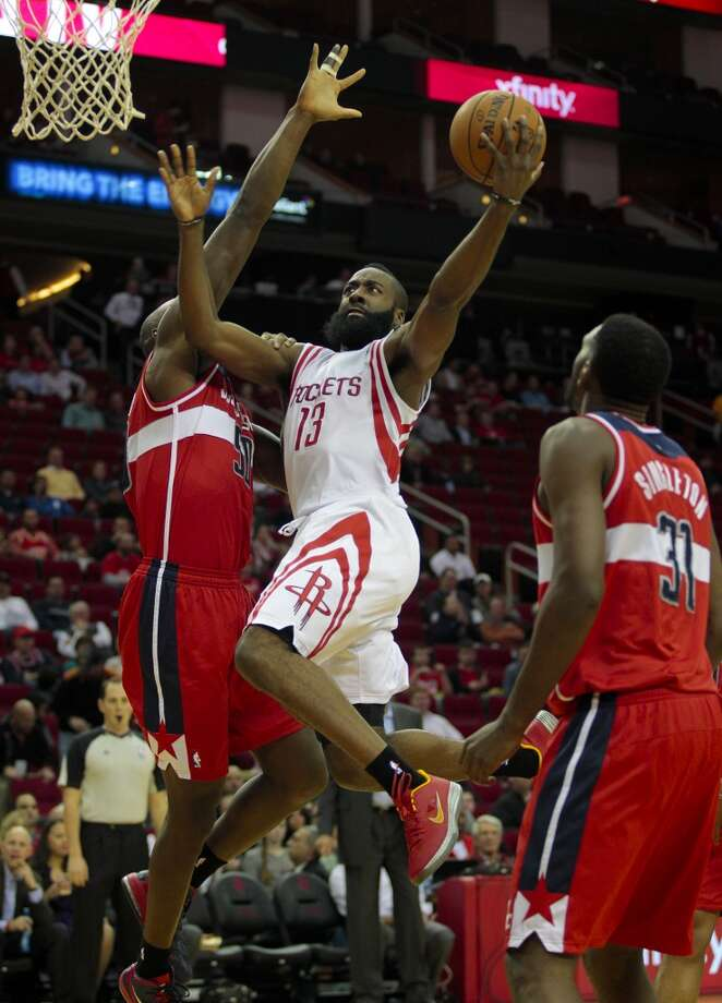 Rockets guard James Harden splits two Wizards' defenders. (Billy Smith II / Houston Chronicle)