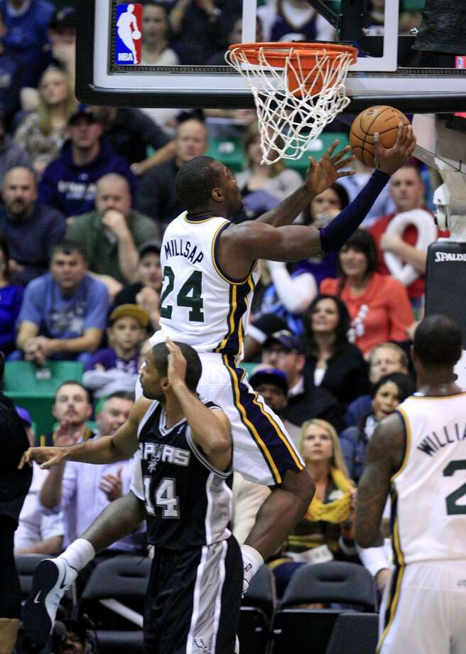 Utah Jazz forward Paul Millsap (24) lays the ball up over San Antonio Spurs guard Gary Neal (14) in the second half during an NBA basketball game Wednesday, Dec.12, 2012, in Salt Lake City. The Jazz defeated the Spurs 99-96.  (Rick Bowmer / Associated Press)