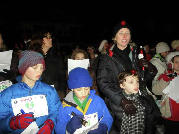 Carolers from the Unitarian Church's One Voice initiative visited 14 homes in the Compo area Wednesday as part of their effort to benefit the Lily Sarah Grace Fund.  Westport CT 12/12/12 Photo: Meg Barone / Westport News freelance