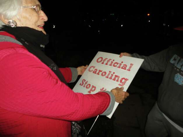 Peg Bishop, who lives on Bradley Street, receives the sign posted in front of her house to alert carolers to stop there as part of their successful effort to set a Guinness World Record for number of people going door-to-door to sing Wednesday night.  Westport CT 12/12/12 Photo: Meg Barone / Westport News freelance