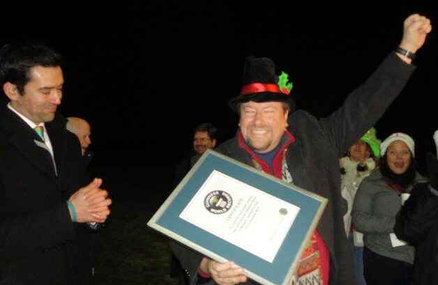 One Voice lead organizer Jim Keenan cheers and holds a certificate acknowledging that the group's effort Wednesday night set a Guinness World Record for mass door-to-door caroling. At left is Danny Girton Jr., an adjudicator for Guinness who observed the effort.  Westport CT 12/12/12 Photo: Meg Barone / Westport News freelance