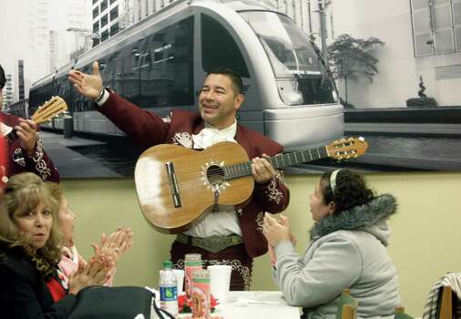 On a chilly afternoon, Alvaro Olvera sings with Mariachi Imperial de America while the faithful enjoy a free lunch after Mass at Holy Cross Chapel in honor of Our Lady of Guadalupe on Wednesday, Dec. 12, 2012, in Houston. Photo: Mayra Beltran, Houston Chronicle / © 2012 Houston Chronicle