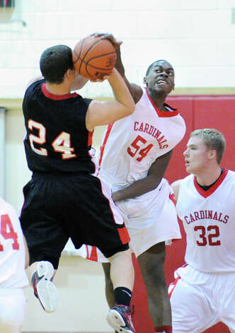 At right, Leonel Hyatt (# 54) of Greenwich blocks the shot of Max Garrett (# 24) of Fairfield Warde during the boys high school basketball game between Greenwich HIgh School and Fairfield Warde High School at Greenwich High School, Wednesday night, Dec. 12, 2012.  At right is Alex Wolf of Greenwich. Photo: Bob Luckey / Greenwich Time