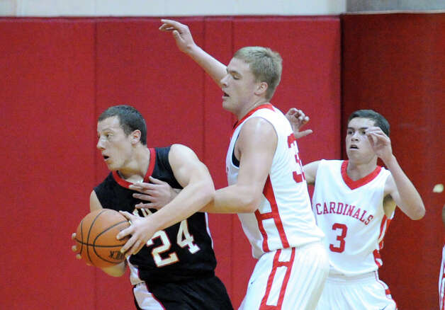 Alex Wolf, center, of Greenwich # 32, defends against Max Garrett, with ball, of Fairfield Warde, as Danny Guise, right, of Greenwich looks on during the boys high school basketball game between Greenwich HIgh School and Fairfield Warde High School at Greenwich High School, Wednesday night, Dec. 12, 2012. Photo: Bob Luckey / Greenwich Time