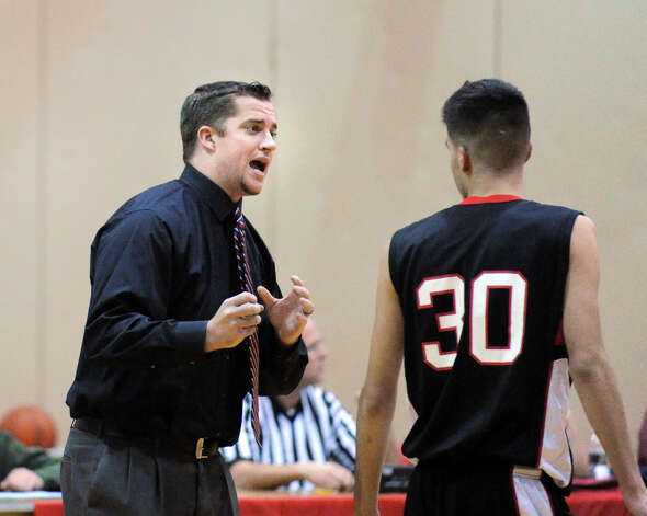 At left, Fairfield Warde High School boys basketball head coach Ryan Swaller speaks with player Nick Cotto (#30) during game between Greenwich HIgh School and Fairfield Warde High School at Greenwich High School, Wednesday night, Dec. 12, 2012. Photo: Bob Luckey / Greenwich Time