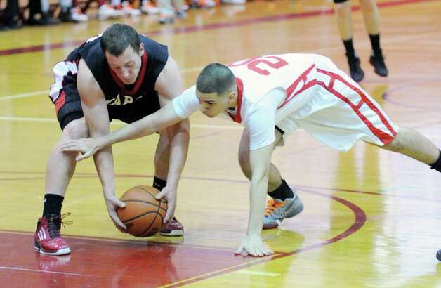 At left, Max Garrett # 24 of Fairfield Warde attempts to protect the ball from a diving Jimmy Djema, right, of Greenwich, during the boys high school basketball game between Greenwich HIgh School and Fairfield Warde High School at Greenwich High School, Wednesday night, Dec. 12, 2012. Photo: Bob Luckey / Greenwich Time