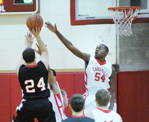 At right, Leonel Hyatt (# 54) of Greenwich just misses the block on a shot attempt by Max Garrett (# 24) of Fairfield Warde during the boys high school basketball game between Greenwich HIgh School and Fairfield Warde High School at Greenwich High School, Wednesday night, Dec. 12, 2012. Photo: Bob Luckey / Greenwich Time