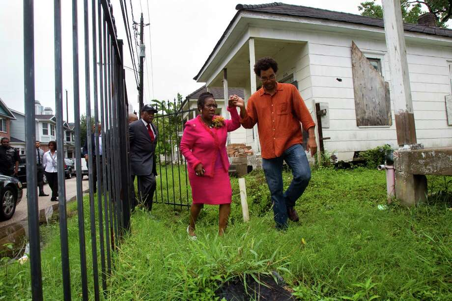 Rick Lowe, right, helps lead Rep. Sheila Jackson Lee into the site of row houses before a news conference Thursday, July 12, 2012, in Houston. Rep. Sheila Jackson Lee and delegates from the NAACP convention visited the site of the shotgun houses, calling for the preservation of the historic homes, and keep them on this site, in historic Freedmen's Town. Photo: Brett Coomer, Houston Chronicle / © 2012 Houston Chronicle
