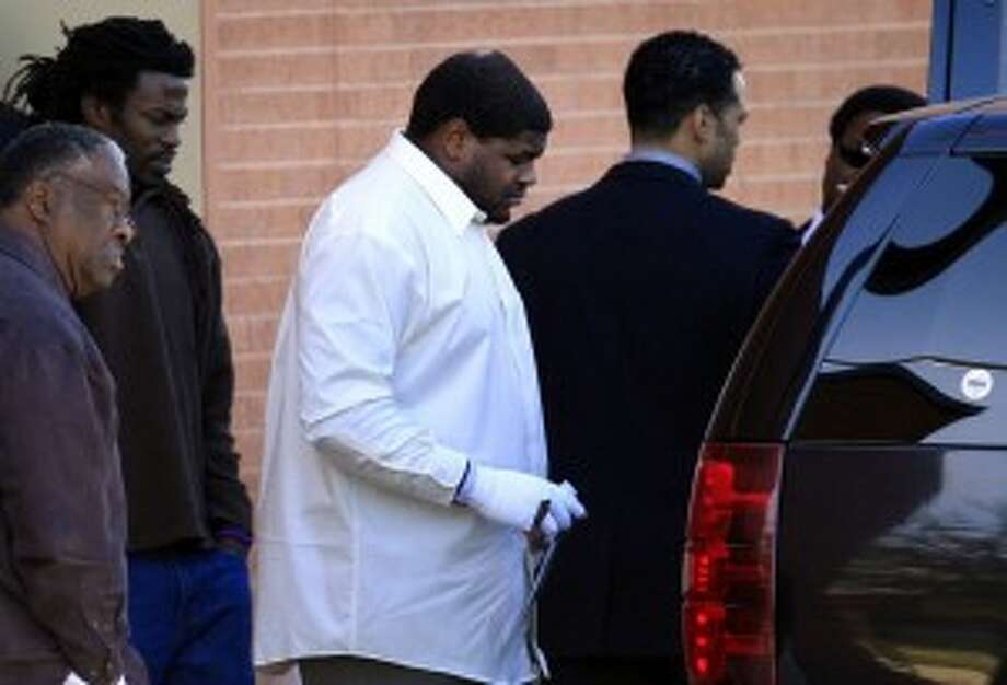 Dallas Cowboys football player Josh Brent, center, with a bandaged hand, leaves with unknown persons after a memorial service for practice squad member Jerry Brown at Oak Cliff Bible Fellowship, Tuesday, Dec. 11, 2012, in Dallas. Brown died in a suspected drunken-driving accident on Saturday. Brent was the driver and is charged with intoxication manslaughter. (AP Photo/LM Otero)