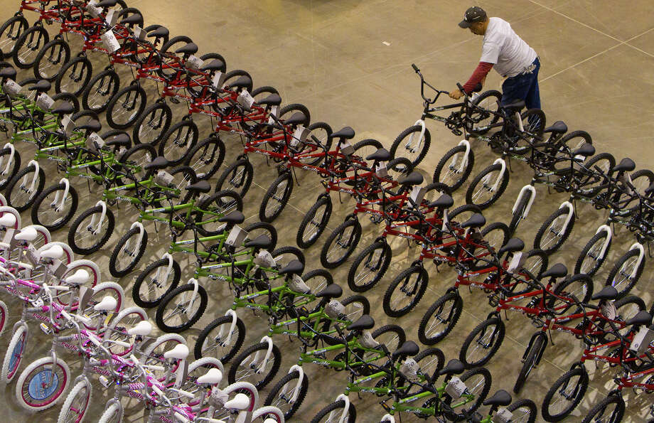 Shane Carpenter stages a bike while volunteering for Elves & More at Reliant Arena Wednesday, Dec. 12, 2012, in Houston. The organization will build and distribute bikes to almost 10,000 at-risk youth in Houston. The child must first sign a contract with a their school teacher and meet one of the five requirements on that contract to receive the bicycle. Photo: Cody Duty, Houston Chronicle / © 2012 Houston Chronicle