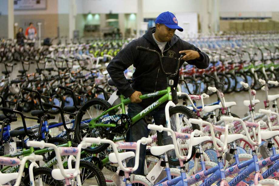 Kris Rollins removes a bike from its line for additional repair while volunteering for Elves & More at Reliant Arena Tuesday, Dec. 11, 2012, in Houston. The organization will build and distribute bikes to almost 10,000 at-risk youth in Houston. The child must first sign a contract with a their school teacher and meet one of the five requirements on that contract to receive the bicycle. Photo: Cody Duty, Houston Chronicle / © 2012 Houston Chronicle