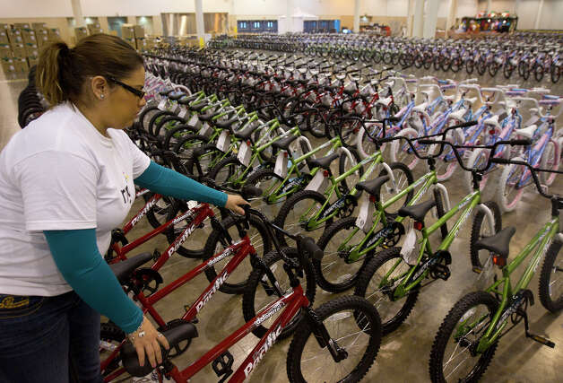 Cynthia Garcia stages a bike while volunteering for Elves & More at Reliant Arena Wednesday, Dec. 12, 2012, in Houston. The organization will build and distribute bikes to almost 10,000 at-risk youth in Houston. The child must first sign a contract with a their school teacher and meet one of the five requirements on that contract to receive the bicycle. Photo: Cody Duty, Houston Chronicle / © 2012 Houston Chronicle