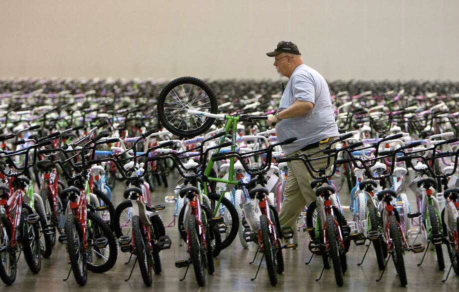 Steven Hutchinson stages a bike while volunteering for Elves & More at Reliant Arena Wednesday, Dec. 12, 2012, in Houston. The organization will build and distribute bikes to almost 10,000 at-risk youth in Houston. The child must first sign a contract with a their school teacher and meet one of the five requirements on that contract to receive the bicycle. Photo: Cody Duty, Houston Chronicle / © 2012 Houston Chronicle