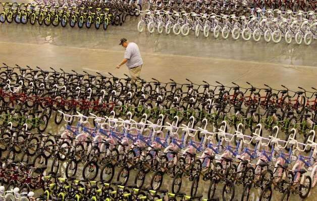 Steven Hutchinson counts a row of bikes while volunteering for Elves & More at Reliant Arena Wednesday, Dec. 12, 2012, in Houston. The organization will build and distribute bikes to almost 10,000 at-risk youth in Houston. The child must first sign a contract with a their school teacher and meet one of the five requirements on that contract to receive the bicycle. Photo: Cody Duty, Houston Chronicle / © 2012 Houston Chronicle