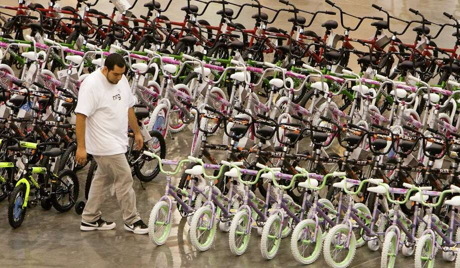 William Gonzalez look at a bike while volunteering for Elves & More at Reliant Arena Wednesday, Dec. 12, 2012, in Houston. The organization will build and distribute bikes to almost 10,000 at-risk youth in Houston. The child must first sign a contract with a their school teacher and meet one of the five requirements on that contract to receive the bicycle. Photo: Cody Duty, Houston Chronicle / © 2012 Houston Chronicle