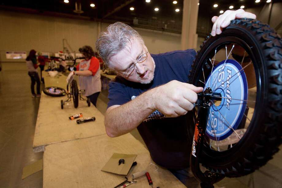 Stephen Ball assembles a bicycle while volunteering for Elves & More at Reliant Arena Tuesday, Dec. 11, 2012, in Houston. The organization will build and distribute bikes to almost 10,000 at-risk youth in Houston. The child must first sign a contract with a their school teacher and meet one of the five requirements on that contract to receive the bicycle. Photo: Cody Duty, Houston Chronicle / © 2012 Houston Chronicle