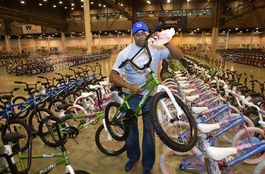Kris Rollins places a bicycle in a row while volunteering for Elves & More at Reliant Arena Tuesday, Dec. 11, 2012, in Houston. The organization will build and distribute bikes to almost 10,000 at-risk youth in Houston. The child must first sign a contract with a their school teacher and meet one of the five requirements on that contract to receive the bicycle. Photo: Cody Duty, Houston Chronicle / © 2012 Houston Chronicle