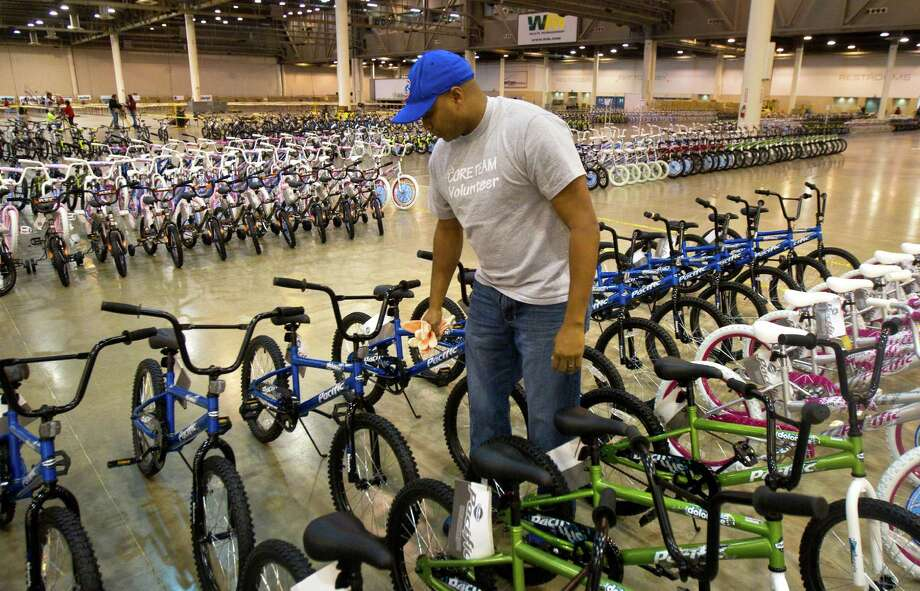 Kris Rollins checks over bicycles for any additional repair while volunteering for Elves & More at Reliant Arena Tuesday, Dec. 11, 2012, in Houston. The organization will build and distribute bikes to almost 10,000 at-risk youth in Houston. The child must first sign a contract with a their school teacher and meet one of the five requirements on that contract to receive the bicycle. Photo: Cody Duty, Houston Chronicle / © 2012 Houston Chronicle