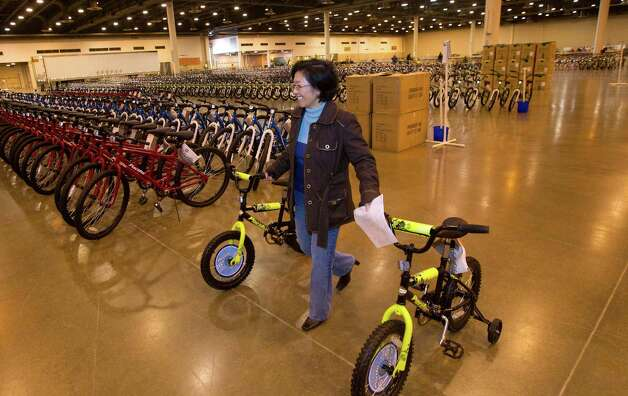 Holly Le walks a bike to its staging area while volunteering for Elves & More at Reliant Arena Tuesday, Dec. 11, 2012, in Houston. The organization will build and distribute bikes to almost 10,000 at-risk youth in Houston. The child must first sign a contract with a their school teacher and meet one of the five requirements on that contract to receive the bicycle. Photo: Cody Duty, Houston Chronicle / © 2012 Houston Chronicle