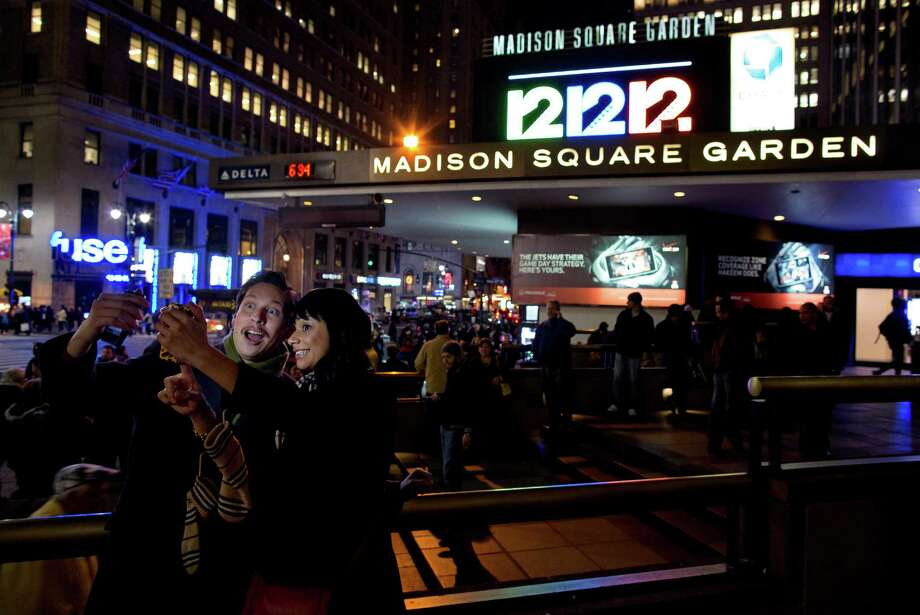 "Friends Steve Ramos, of Los Angeles, and Viviana Barraza, of Bridgeport, Conn., take a photo of themselves before attending the ""12-12-12"" benefit concert at Madison Square Garden in New York Wednesday, Dec. 12, 2012. Music royalty from the Rolling Stones to Kanye West are gathering at Madison Square Garden for a benefit concert to help storm victims. (AP Photo/Craig Ruttle) Photo: Craig Ruttle, Associated Press / Associated Press"