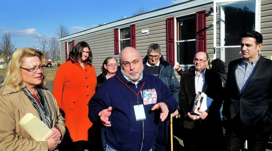New Fairfield First Selectman John Hodge, center, speaks about temporary shelter for Hurricane Sandy victims from Staten Island, N.Y.,who stand behind him during a press confersence at Faith Church in New Milford Thursday, Dec. 13, 2012. Mobile homes are being brought to church property and utilities are being installed so families can move in later this month. New Milford Mayor Pat Murphy, left, and Faith Church Pastor Frank Santora, right, listen. Photo: Michael Duffy / The News-Times