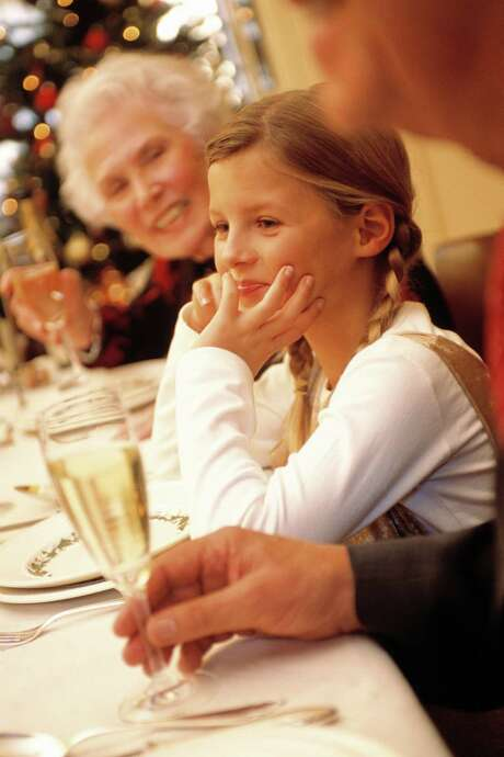 Table manners are important at holiday meals. Lizzie Post suggests practicing with your children. Little Girl at Christmas Dinner --- Image by  ImageShop/Corbis Photo: --
