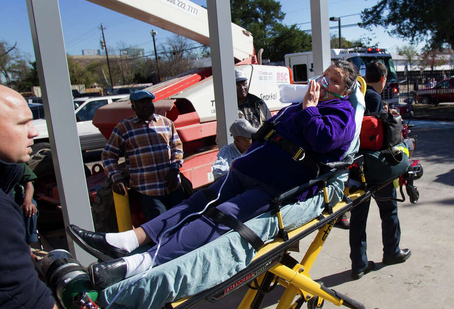 A woman is prepared for to be transported after a two-alarm fire started in an assisted-living facility on Lyerly Street, Thursday, Dec. 13, 2012, in Houston. Photo: Cody Duty, Houston Chronicle / © 2012 Houston Chronicle
