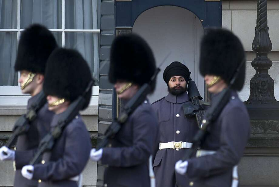 A little less on top: Sikh Scots Guards soldier Jatenderpal Singh Bhullar stands guard outside Buckingham Palace as other palace guardsmen march by. Bhullar is the first guardsman to to wear a turban instead of the bearskin on duty. Photo: Carl Court, AFP/Getty Images