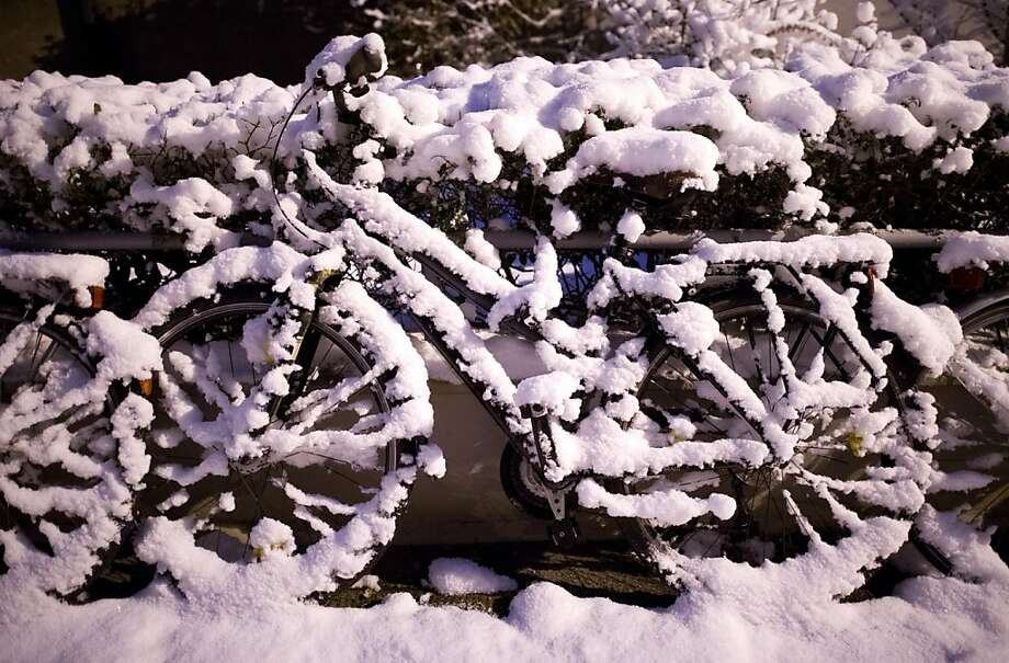 Too cold for pedaling:Wet snow covers a bicycle in Hannover, Germany. Photo: Julian Stratenschulte, AFP/Getty Images