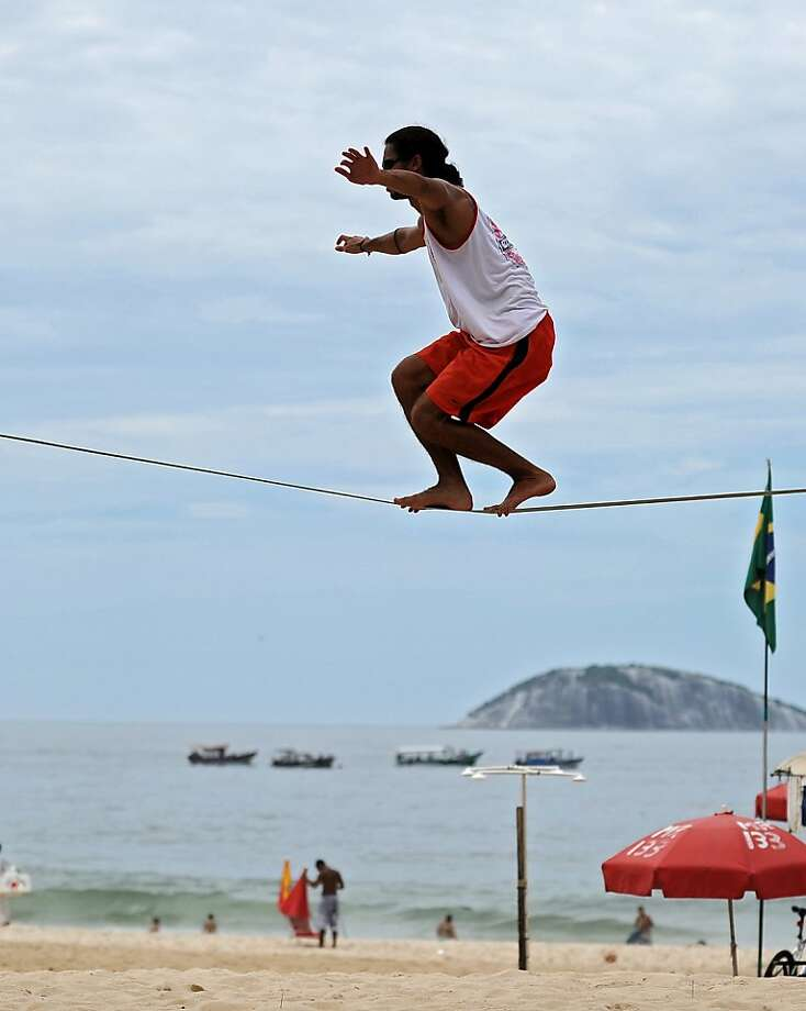 Walking a fine line:A man balances on a slack rope between two palm trees on Ipanema beach in Rio de Janeiro. Photo: Vanderlei Almeida, AFP/Getty Images