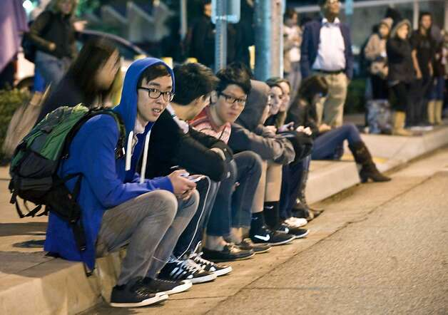 Evacuated students sit on a curb Wednesday outside the College of Business and Economics. Photo: Bruce Chambers, Associated Press