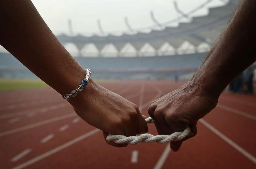 A helping hand: A blind track athlete (left) and her guide prepare to run in a race at the 18