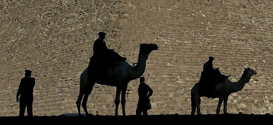 The camel patrol: Mounted and foot police keep the peace at the Great Pyramids in Giza, Egypt. An opposition alliance urged supporters to vote against a new constitution in a referendum. Photo: Hassan Ammar, Associated Press