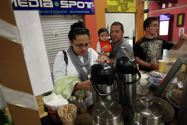 Marissa Gonzalez, 29, pours a cup of coffee at a cafe inside PicaPica Plaza, a mercado consisting of more than 200 small and family-owned businesses, Sunday, Dec. 9, 2012. The plaza is located in a building that used to house a Wal-Mart at 910 SE Military Drive. Next to Gonzalez is her daughter, Aryana, 9 months, (cq), and husband, Christopher, 43. On the right is Chris Garcia, 25. Photo: Jerry Lara, San Antonio Express-News / © 2012 San Antonio Express-News