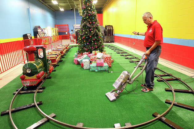 Robert Sandoval vaccums the carpet at the train ride inside PicaPica Plaza, a mercado consisting of more than 200 small and family-owned businesses, Sunday, Dec. 9, 2012. The plaza is located in a building that used to house a Wal-Mart at 910 SE Military Drive. Photo: Jerry Lara, San Antonio Express-News / © 2012 San Antonio Express-News