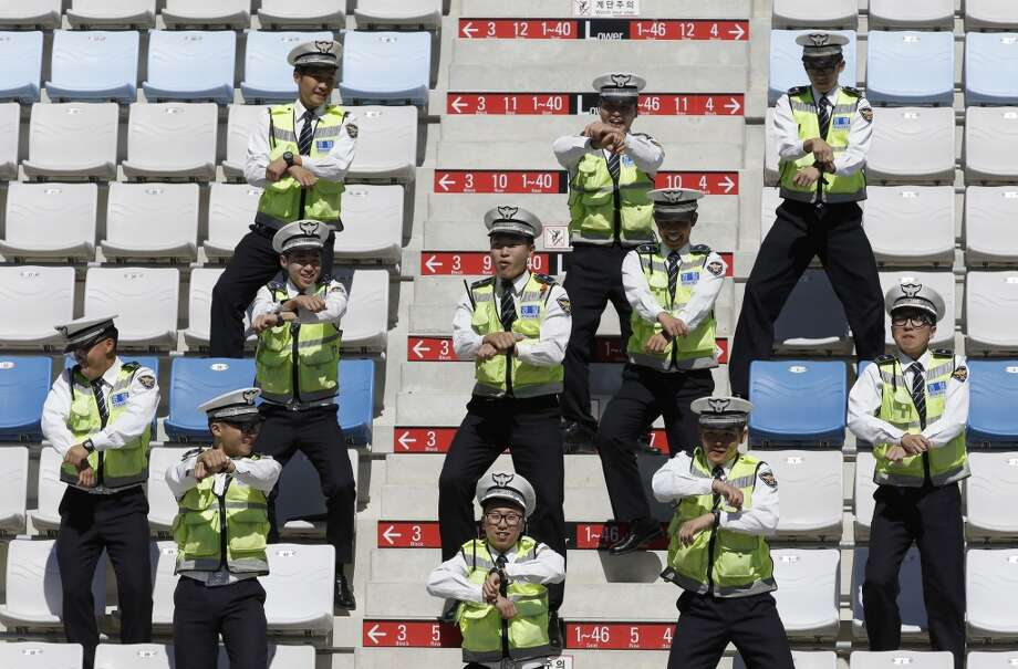 South Korean police officers dance South Korean rapper PSY's  Gangnam Style dance in the grandstand ahead of the Korean Formula One Grand Prix at the Korean International Circuit in Yeongam, South Korea, Thursday, Oct. 11, 2012.  (Associated Press)