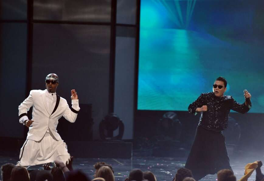 "MC Hammer, left, dances as PSY performs ""Gangnam Style"" at the 40th Anniversary American Music Awa"