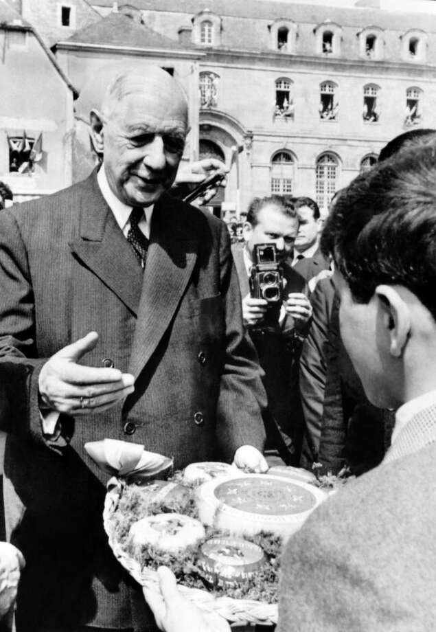 French President Charles de gaulle receives a cheeseboard while visiting Mamers, western France, on May 22, 1965. Photo: -, AFP/Getty Images / 2010 AFP
