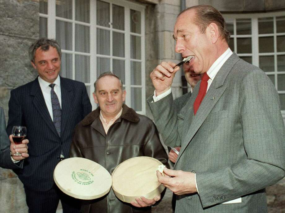French President Jacques Chirac smiles while testing Mont-d'Or cheese on December 27, 1987 in Besançon, France. Photo: ERIC FEFERBERG, AFP/Getty Images / 2012 AFP