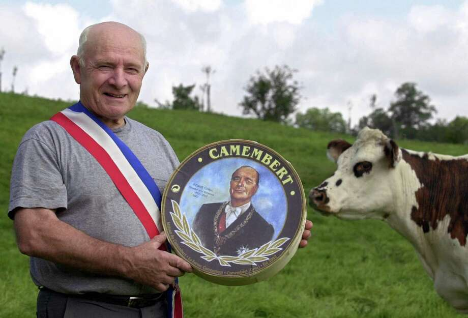 Camembert, France, Mayor Jean Gaubert poses with a Camembert cheese box showing a portrait of French president Jacques Chirac on July 11, 2002. Photo: ROBERT FRANCOIS, AFP/Getty Images / 2003 AFP