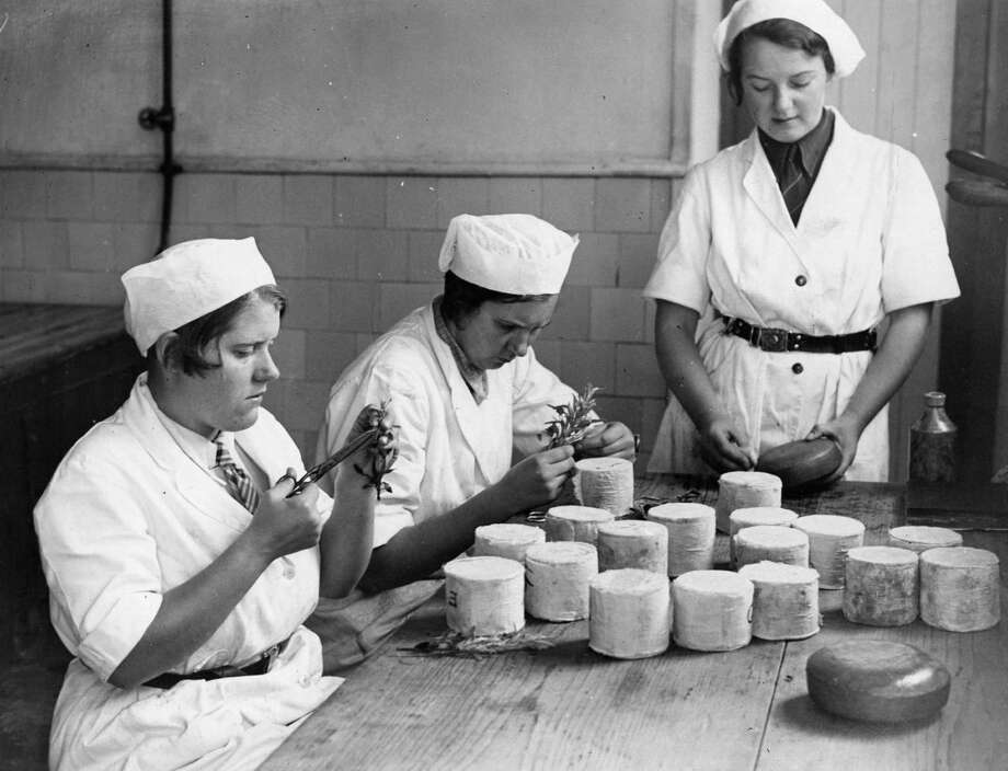 Students of dairy farming at Studley College in Warwickshire, England, decorate cheeses with designs cut from herb leaves on October 19, 1935 in preparation for the Dairy Show at the Agricultural Hall in London. Photo: Fox Photos, Getty Images / Hulton Archive